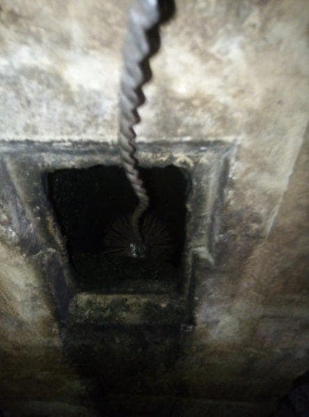 Cleaning the chimney with a brush downwards